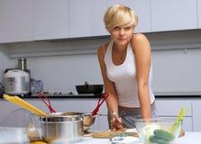 Recht blondes Mädchen in der Küche, die Teigwaren bildet Stockfoto