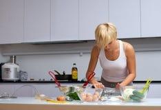 Recht blondes Mädchen in der Küche, die Teigwaren bildet Lizenzfreie Stockfotografie