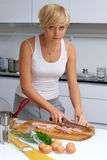 Recht blondes Mädchen in der Küche, die Teigwaren bildet Stockbild