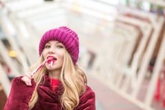 Recht blondes Mädchen in der roten Strickmütze, die mit Weihnachten-cand aufwirft Lizenzfreies Stockbild
