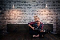 Recht blondes Mädchen in der verursachenden Kleidung, die Musik auf Gitarre spielt Stockbilder