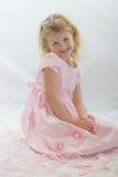 Recht blondes Mädchen im rosafarbenen Sitzen in den rosafarbenen Blumenblättern. Lizenzfreie Stockfotografie