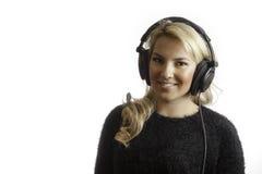 Recht blondes Mädchen-lokalisierten lächelnde tragende Studio-Kopfhörer Hintergrund Stockfotos