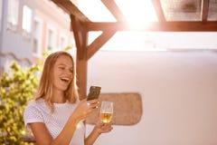 Recht blondes Mädchen mit Bier und Mobiltelefon Stockfotografie