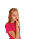 Recht blondes Mädchen mit dem Finger über Mund Stockfoto