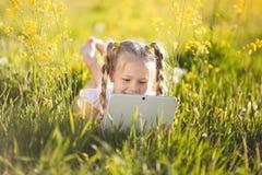 Recht blondes Mädchen mit digitaler Tablette auf dem gelben Gebiet Lizenzfreie Stockfotografie