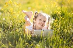 Recht blondes Mädchen mit digitaler Tablette auf dem gelben Gebiet Lizenzfreie Stockbilder