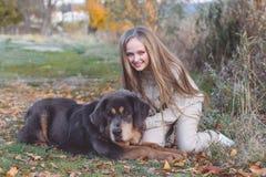 Recht blondes Mädchen mit Mastiff auf der Natur Stockfoto