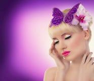 Recht blondes Mädchen mit Orchideenblume und -schmetterling Stockfotografie