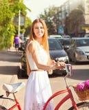 Recht blondes Mädchen mit Retro- Blick, Fahrrad und Korb mit Blumen Stockfoto