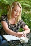 Recht blondes Mädchen mit Tagebuch Stockfotos