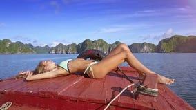 Recht blondes Mädchen nimmt ein Sonnenbad nehmen auf Boot gegen durchaus Bucht stock video footage