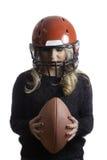Recht blondes Mädchen-roter Sturzhelm, der Fußball lokalisierten Hintergrund hält Stockbild