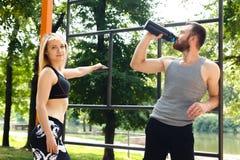 Recht blondes Mädchen und bärtiger Mann, die nach Training trainin stillsteht Lizenzfreie Stockbilder