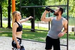 Recht blondes Mädchen und bärtiger Mann, die nach Training trainin stillsteht Stockfotos