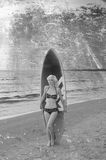Recht blondes Mädchenmodell mögen Marilyn Monroe mit surfendem Brett auf einem Strand Stockbilder