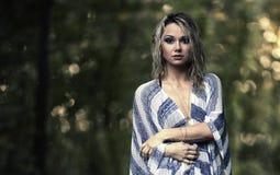 Recht blondes Modell, das in einer Waldreinigung aufwirft Stockbild