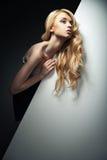 Recht blondes Modell, das hinter einem großen Blatt von sich versteckt Stockfotografie