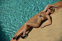Recht blondes Modell, das sich am Rand des Swimmingpools hinlegt Stockfotografie