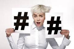 Recht blondes Modell, das zwei hashtag Zeichen auf Papier zeigt Stockbild