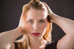 Recht blondes Modell im schwarzen Kleid, das Hände im Haar aufwirft Stockfoto