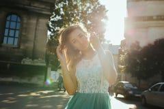 Recht blondes Modell im Spitzekleid, das in der Sonne aufwirft, strahlt am stre aus Stockbild