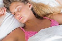 Recht blondes Schlafen im Bett Lizenzfreie Stockfotos