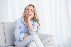 Recht blondes Sitzen auf dem Couchdenken Lizenzfreie Stockfotografie