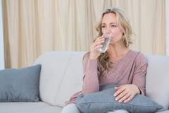 Recht blondes Sitzen auf Trinkwasser der Couch Lizenzfreies Stockbild