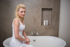 Recht blondes Sitzen durch das Bad, das an der Kamera lächelt Stockbilder
