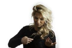 Recht blondes verwirrtes Versuchen, Haar mit Zangen zu schneiden Lizenzfreie Stockbilder