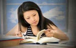 Recht chinesische asiatische Lesung des jungen Mädchens und mit Schulbüchern und Studioschreibtisch des Computerlaptops zu Hause  Stockbilder