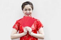 Recht chinesische Frau, die rote Beutel anhält Lizenzfreie Stockfotografie