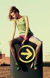 Recht dünne Frau, die auf Straßenschauzeichen sitzt Lizenzfreie Stockfotos