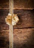Recht dekorativer Goldbogen über Holz Stockfotos