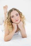 Recht durchdachtes blondes Lügen auf dem Bett, das Kamera betrachtet Lizenzfreie Stockfotos