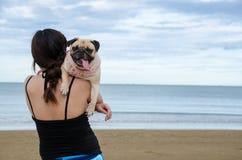 Recht einsamer Asien-Mädchengriff ein netter Hundewelpe Pug gegen Strand- und Himmelhintergrund Stockfotografie