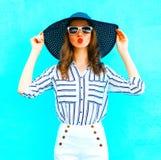 Recht elegante Frau, die einen Strohhut, weiße Hosen trägt Lizenzfreie Stockfotos