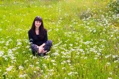 Recht entspannte Frau auf dem Blumenfeld Stockfotografie