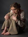 Recht erschraken Armen Mädchen in der ukrainischen Stickerei, die auf dem Boden sitzt Lizenzfreie Stockfotografie