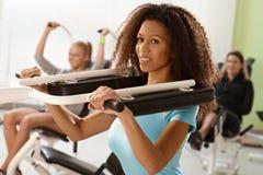 Recht ethnisches Mädchen, das auf Gewichtmaschine trainiert Stockfoto