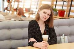Recht europäische Frau trinkt Milchshake im Café, trägt schwarze stilvolle Tupfenbluse, genießt Erholungszeit mit Freunden beaut lizenzfreie stockbilder