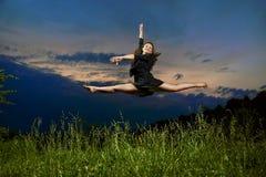 Recht führen Junge, lächelnder Tänzer Spalten in der Luft durch Lizenzfreie Stockfotos