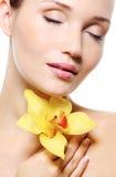 Recht frisches sauberes weibliches Gesicht mit einer Blume Stockbild