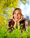 Recht frohes junges Mädchen, das auf grünem Gras liegt Stockfotos