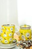 Recht gelber Teesatz mit Staplungsschalen, Untertassen und Topf, Blumenverzierung, rustikale Küche Innen, weiche Sonnenlichtstell Stockbild