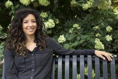 Recht gelockte behaarte Frau auf dem Park-Bank-Lächeln Stockbild
