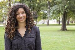 Recht gelockte behaarte Frau beim Park-Lächeln Stockfotografie