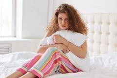 Recht gelockte Frau in den Pyjamas, hält weißes Kissen in den Händen, Gebühr stockfoto