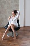 Recht gesellige Frau im weißen Hemd, das auf Lehnsessel sitzt Stockfotos